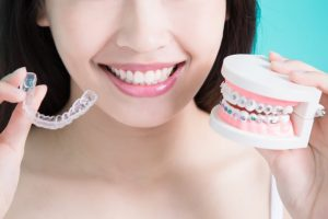 person holding Invisalign aligners and braces