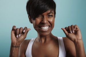 attractive woman smiling while flossing teeth