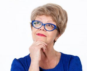 older woman blue glasses thinking