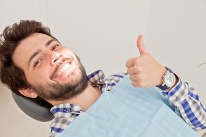 young man smiling sitting in dentist chair after dental checkup