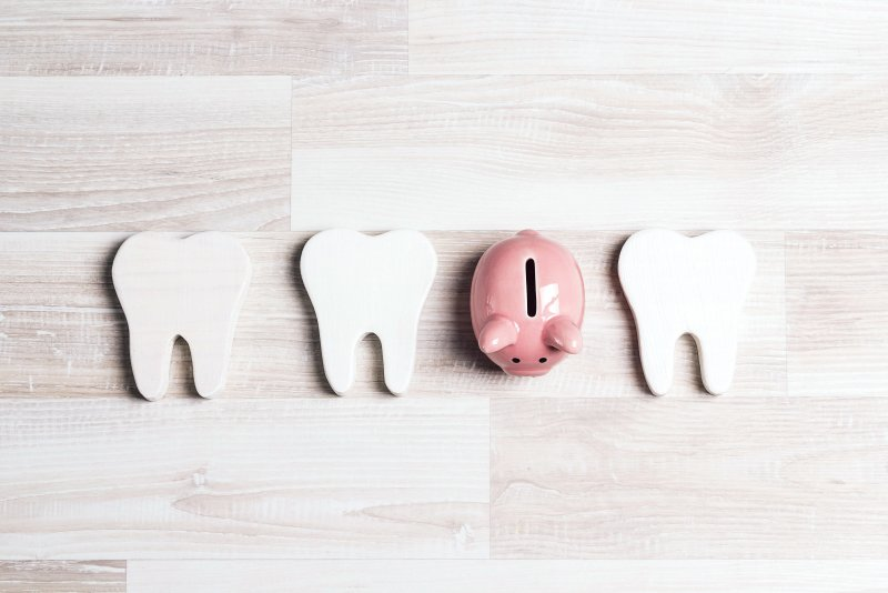 Piggy bank next to cardboard teeth